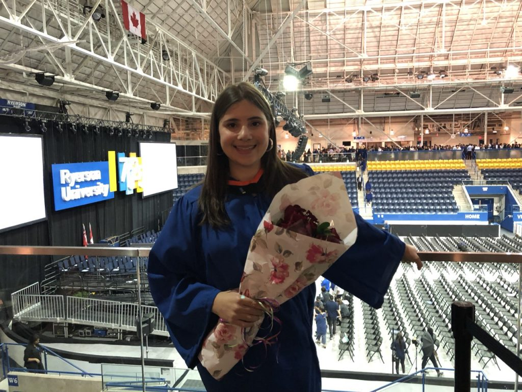 Photo of Jackie at her graduation from Ryerson's BASc Nutrition in June 2018. Jackie is standing and is wearing a navy blue graduation gown and holding a bouquet of flowers. There is a large stadium behind her with Ryerson's blue and yellow logo colours.