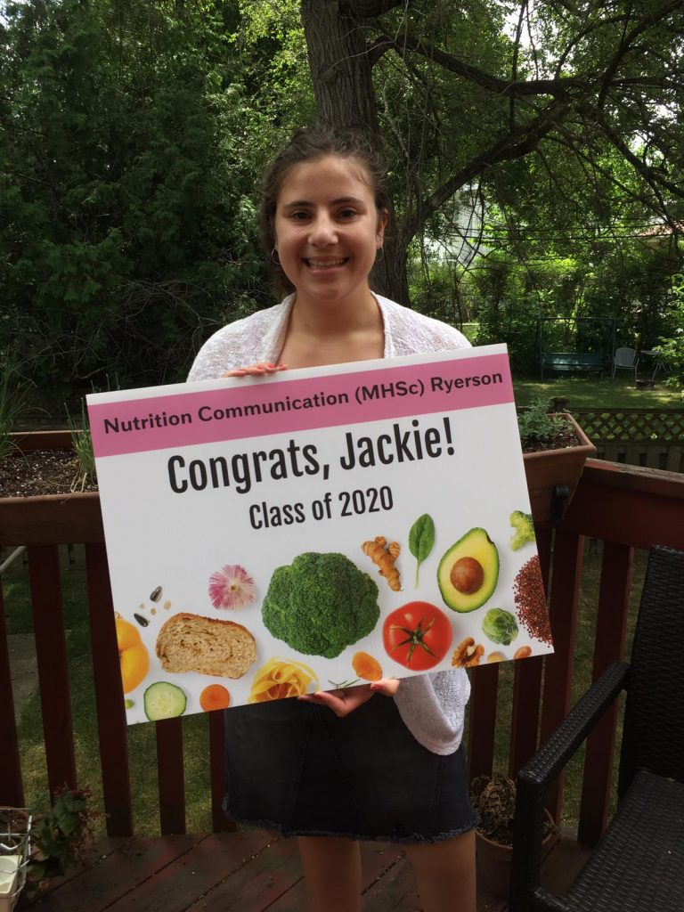 """Photo of Jackie taken in her backyard in June 2020 in lieu of a graduation ceremony from her master's degree, which was cancelled due to COVID-19. She is holding up a sign that her family had printed for her that says """"Nutrition Communication (MHSc) Ryerson - Congrats, Jackie! - Class of 2020."""""""