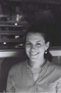 A black and white photo of a woman in a ponytail wearing a button up shirt is smiling in the camera