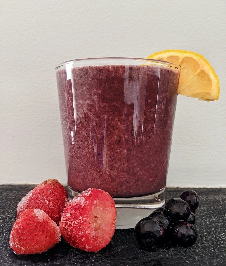 A glass of chocolate berry smoothie with strawberries, blueberries, and lemon