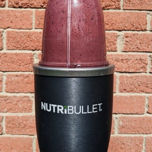 Chocolate berry smoothie in a NutriBullet in front of a brick wall