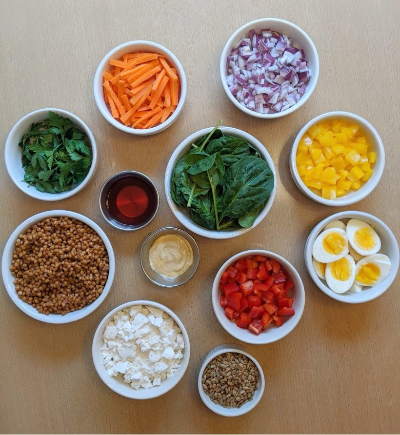 Bowls of lentils, carrots, red onions, red peppers, yellow peppers, parsley, sunflower seeds, feta cheese, spinach, hard boiled eggs with red wine vinegar and dijon mustard