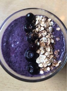 A glass of blueberry pie smoothie topped with blueberries and rolled oats