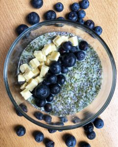 A glass of matcha chia pudding topped with white chocolate and blueberries