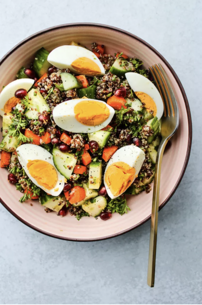 A bowl of Cold Chopped Quinoa Salad with Eggs with a golden fork