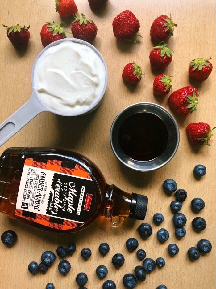 A cup of Greek yogurt, maple syrup, strawberries, and blueberries on a wooden table