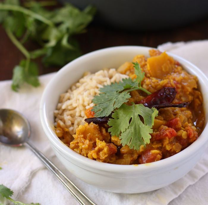 A bowl of Red Lentil Pumpkin Dal topped with cilantro with a silver spoon
