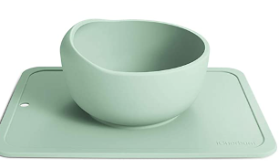 A mint green scoop bowl on a silicone mat suction base
