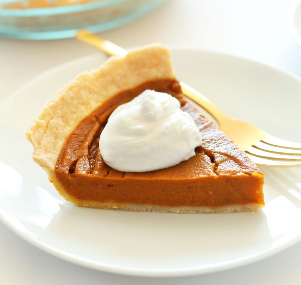 A slice of Vegan Pumpkin Pie topped with coconut whipped cream on a white plate with a golden fork