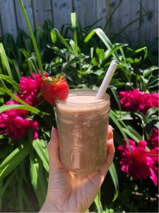 A hand is holding a glass of Yogurt Peanut Butter Smoothie in front of a garden