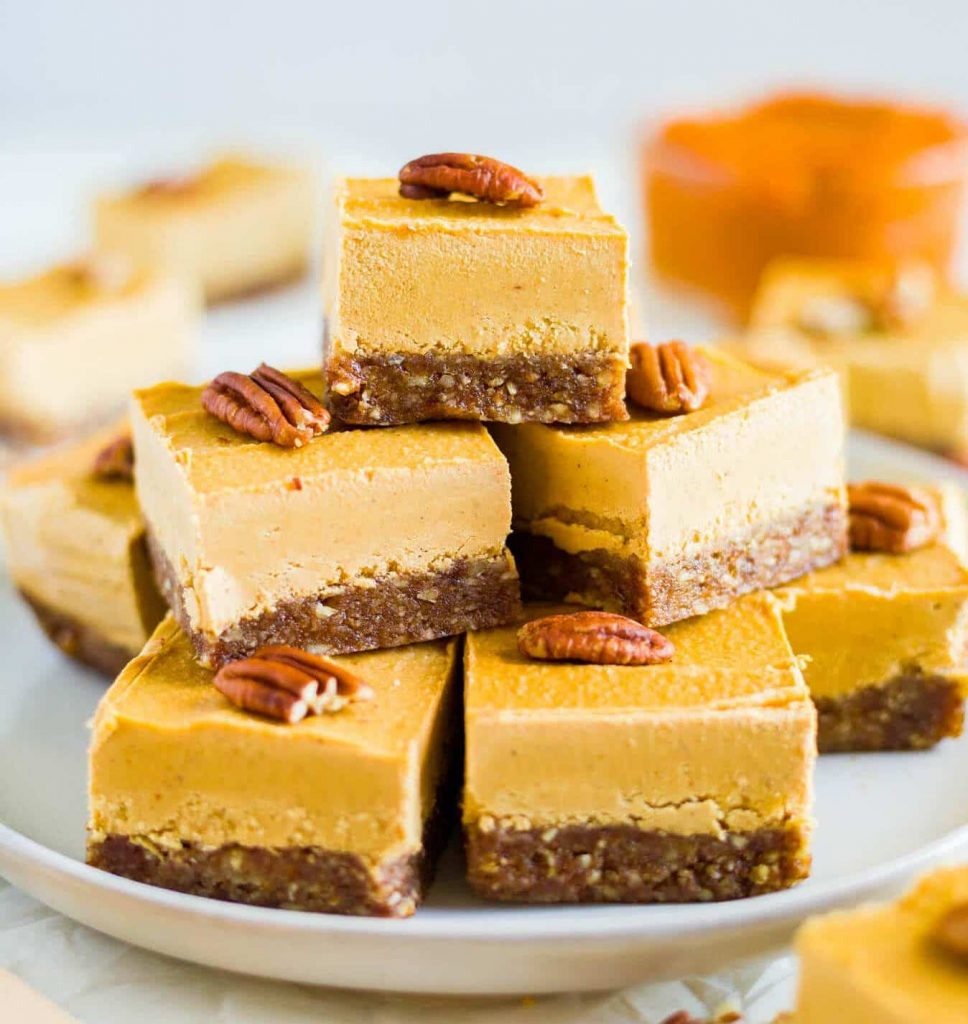 A stack of Vegan Pumpkin Cheesecake Bars topped with pecans on a white plate