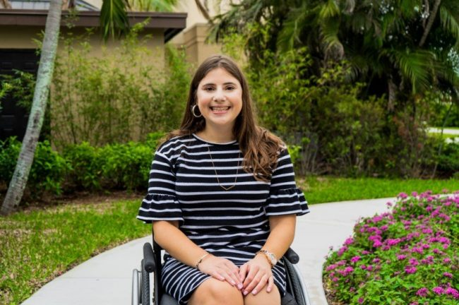 Jackie Silver is sitting on a wheelchair outdoors smiling